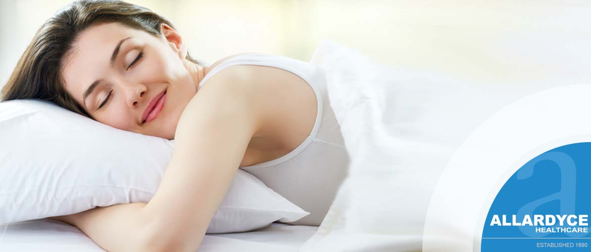 Female in bed smiling with white covers