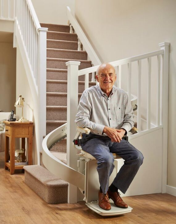 Elderly gentleman smiling, sat on chairlift at bottom of stairs.
