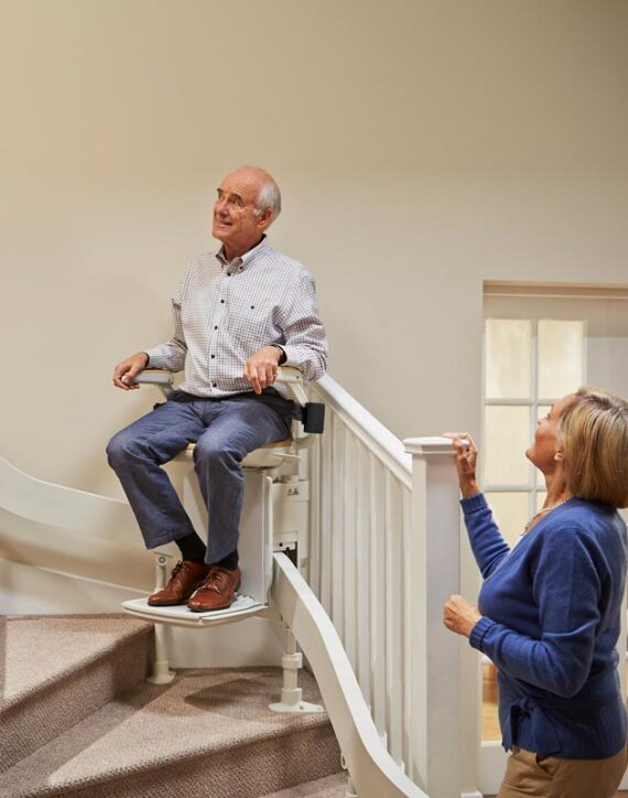 Elderly gentleman on chairlift, lady at bottom of stairs watching him.