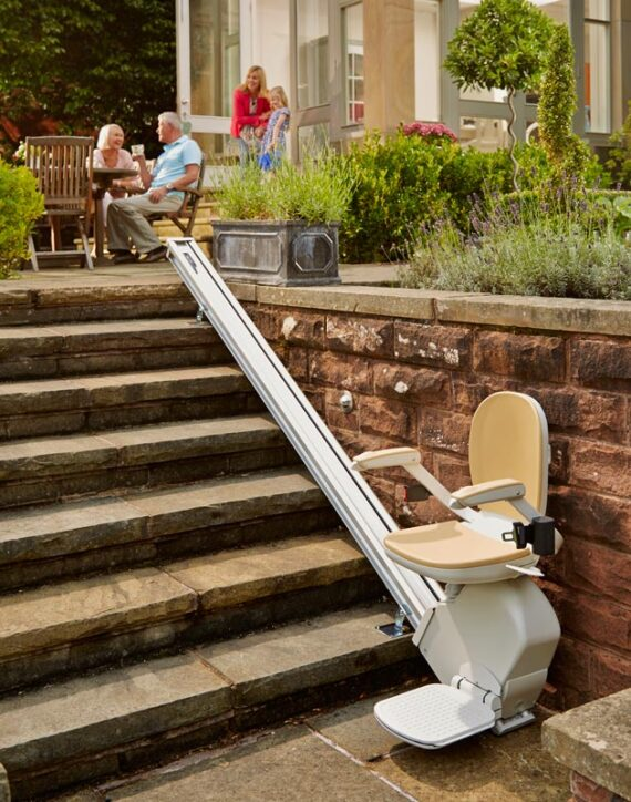 Acorn Chairlift fitted on outside wall. Family relaxing on patio.