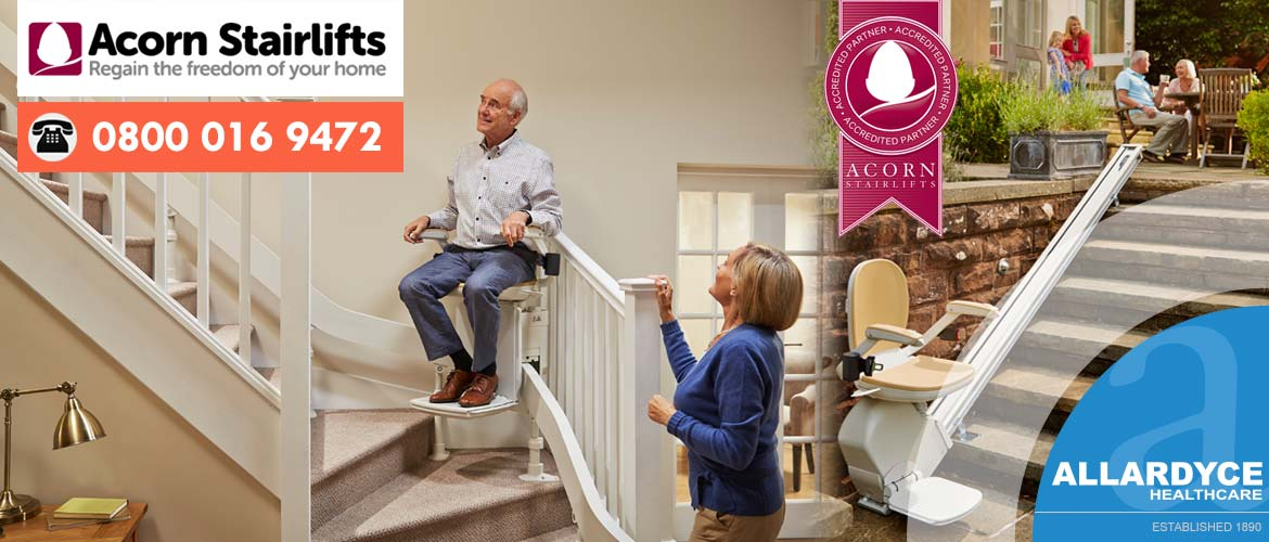 Acorn Stairlifts banner with elderly man in stairlift looking happy as female looks on.