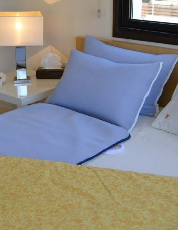 Blue bed overlay on bed with lamp on bedside table.