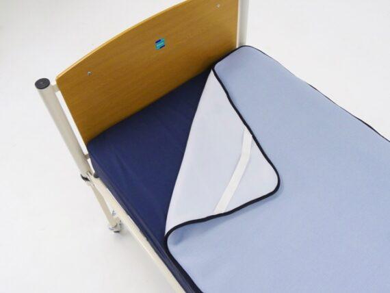 Pale blue bed overlay on dark blue mattress.